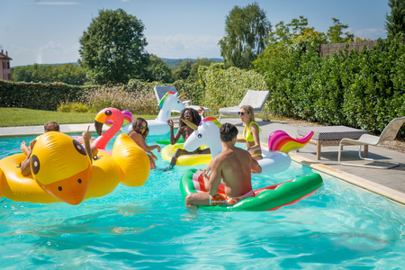 Gemischtrassige Gruppe Freunde, die Partei in einem privaten Landhaus mit Swimmingpool haben - glückliche junge Leute, die mit geformten Luftmatratzen kühlen Standard-Bild - 93324385