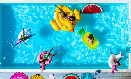Gelukkige mensen feesten in een exclusief zwembad met matten van dieren en fruit, van bovenaf bekijken Stockfoto - 93312191