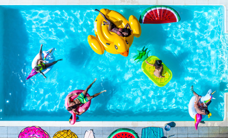 Happy people partying in an exclusive swimming pool with animal and fruit shapes mats, view from above Stock Photo - 93312191