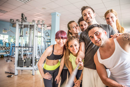 Group of sportive people in a gym taking selfie - Happy sporty friends in a weight room while training - Concepts about lifestyle and sport in a fitness club Stockfoto