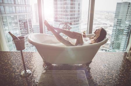 Mujer seductora tomando relajante baño en su bañarse.