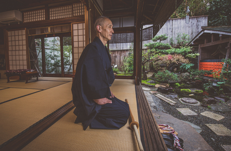 Japanese man meditating in his garden