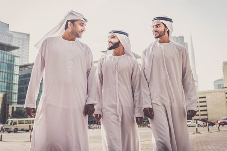 屋外でボンディングする3人のアラビア人男性 - ドバイで歩いたり話したりするビジネスマン 写真素材