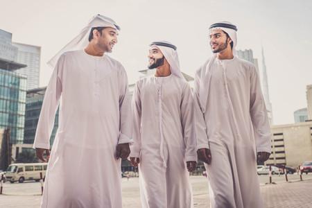 실외에 묶여있는 세 명의 아랍어 남자 - 걷고 두바이에서 이야기하는 사업 사람들