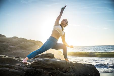 Woman training yoga on the beach at sunset Stock Photo - 93838825