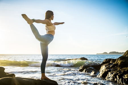 Woman training yoga on the beach at sunset Stock Photo - 93811958