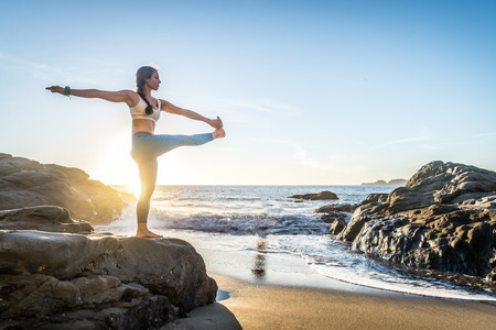 Woman training yoga on the beach at sunset Stock Photo - 93813111