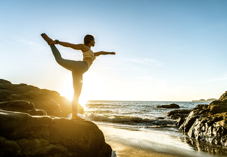 Woman training yoga on the beach at sunset