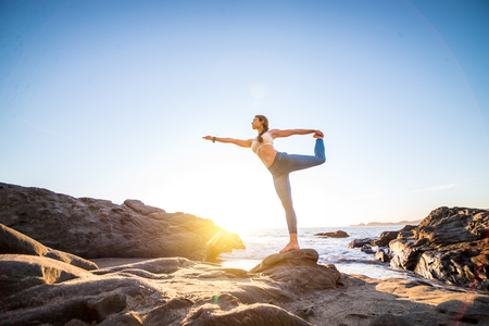 Woman training yoga on the beach at sunset Stock Photo - 93838859