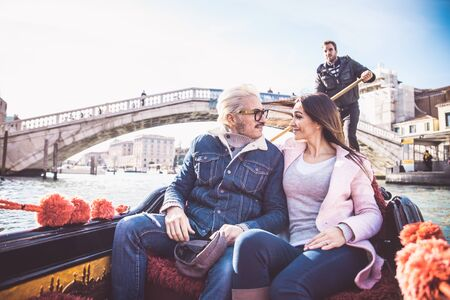 Couple of lovers on vacation in Venice, Italy - Tourists having a trip on a venetian gondola