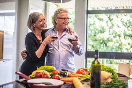 Starsza para gotuje zdrowego jedzenie i pije czerwone wino przy domową kuchnią Zdjęcie Seryjne