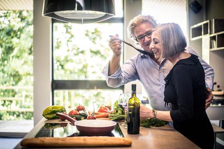 Pareja Senior cocinando comida saludable y bebiendo vino tinto en la cocina de la casa