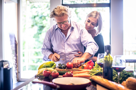 Senior couple cooking healthy food and drinking red wine at house kitchen
