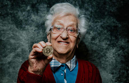 Old woman portrait holding a Cryptocurrency coin Stock Photo