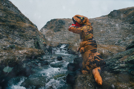 Man With dinosaur costume in a wild natural area