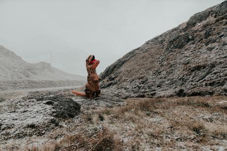 야생 자연 지역에서 공룡 의상을 가진 남자 스톡 콘텐츠