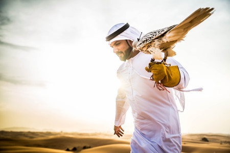 Arabian man walking  in the desert at sunrise