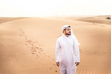 Arabian man walking  in the desert at sunrise