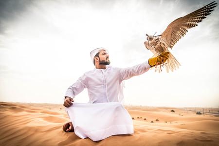 Arabian man walking  in the desert at sunrise Stock Photo - 95676865