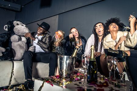 Multi-ethnic group of friends celebrating in a nightclub - Clubbers having party Stock Photo