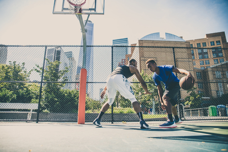 Two afroamerican athlethes playing basketball outdoors - Basketball athlete training on court in New York Stock Photo