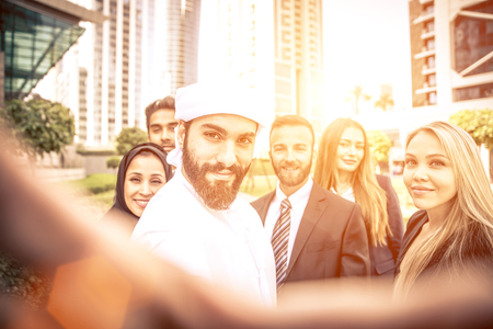 Arabic and western business people taking selfie
