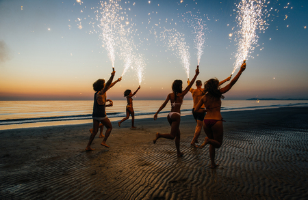 Group of friends having fun running on the beach with sparklers Stock Photo - 97106115