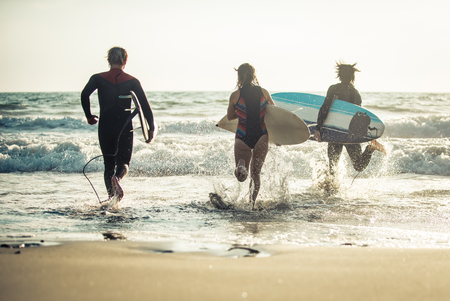 Three surfers practicing in the ocean