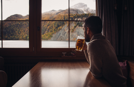 Man drinking beer in  his mountain cabin Stock Photo