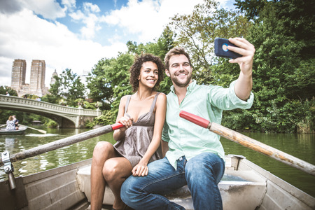 Happy couple having fun on a boat in Central Park - Interracial couple taking a selfie while sightseeing Manhattan Stok Fotoğraf