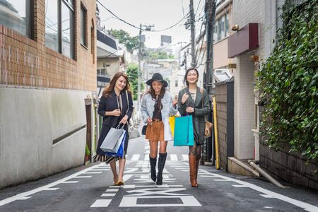 Three women doing shopping outdoors - Best friends meeting while shopping in Tokyo