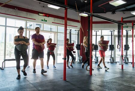 Muscular athletes training in a crossfit gym - Functional training workout in a gym Stock Photo