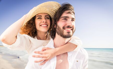 Couple strolling at the beach and smiling - Young adults enjoying summer holidays on a tropical island Stock fotó
