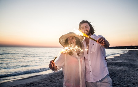 Couple strolling at the beach and smiling - Young adults enjoying summer holidays on a tropical island Stock Photo