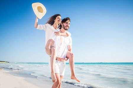 Couple strolling at the beach and smiling - Young adults enjoying summer holidays on a tropical island Stok Fotoğraf