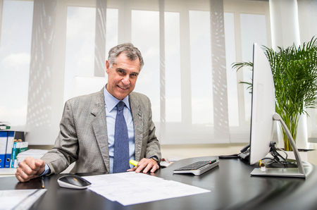 senior businessman sitting at computer desk in his office