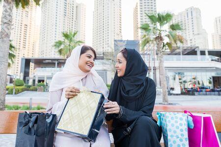 Arabic women shopping outdoors in Dubai - Girls with traditional arabian dress having fun Stock Photo