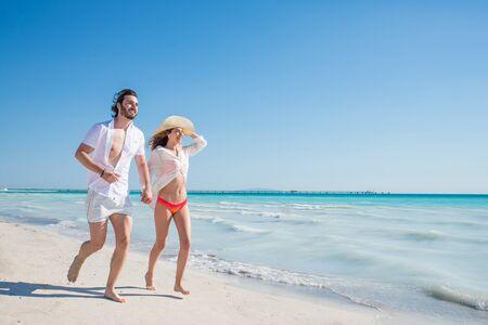 해변에서 산책하고 웃는 커플-열대 섬에서 여름 휴가를 즐기는 젊은 성인