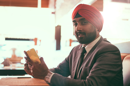 Indian businessman in a cafe taking a coffee Stock Photo