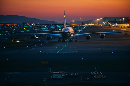 Airplane on the track at sunset time Stock Photo