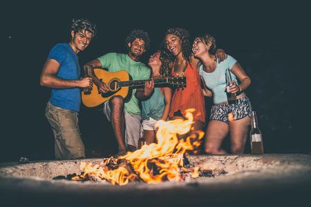 ビーチでパーティーをする友人の多文化グループ - 夏休み、夏休み、休日のコンセプトの間に祝う若者 写真素材