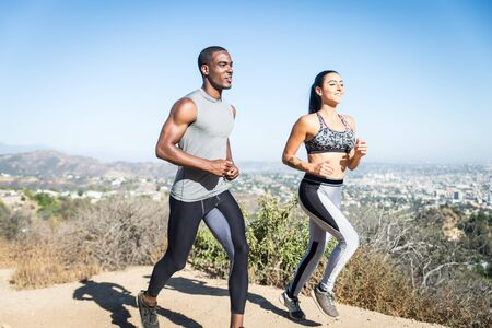 Multi-ethnic couple training in a canyon - Sportive boyfriend and girlfriend running outdoors