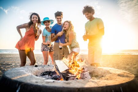 Multicultural group of friends partying on the beach - Young people celebrating during summer vacation, summertime and holidays concepts 스톡 콘텐츠