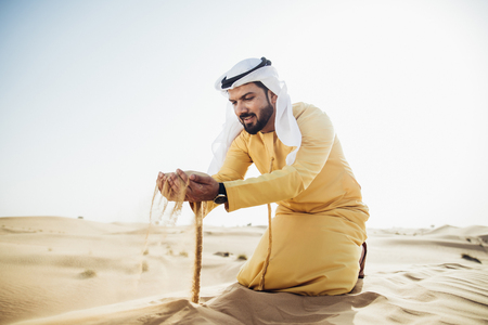 Man wearing traditional uae clothes spending time in the desert 스톡 콘텐츠