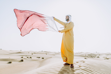 Man wearing traditional uae clothes spending time in the desert Stock Photo