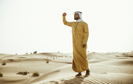 Man wearing traditional uae clothes spending time in the desert Stock fotó