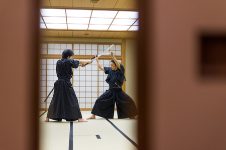 Japanese martial arts athlete training kendo in a dojo - Samaurai practicing in a gym Stock Photo