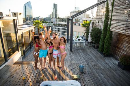 Multiethnische Gruppe von Freunden, die auf dem Dach feiern - Glückliche Menschen, die sich verbinden und Spaß haben