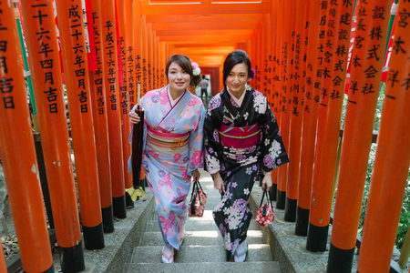 Two beautiful girls with traditional dress walking outdoors 新聞圖片