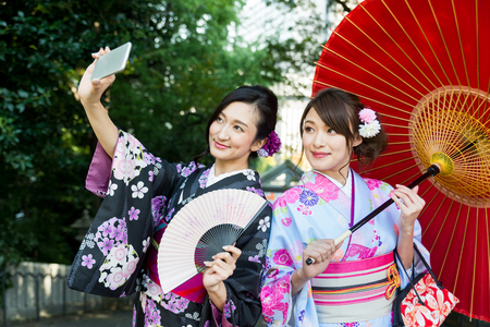 Two beautiful girls with traditional dress walking outdoors 写真素材